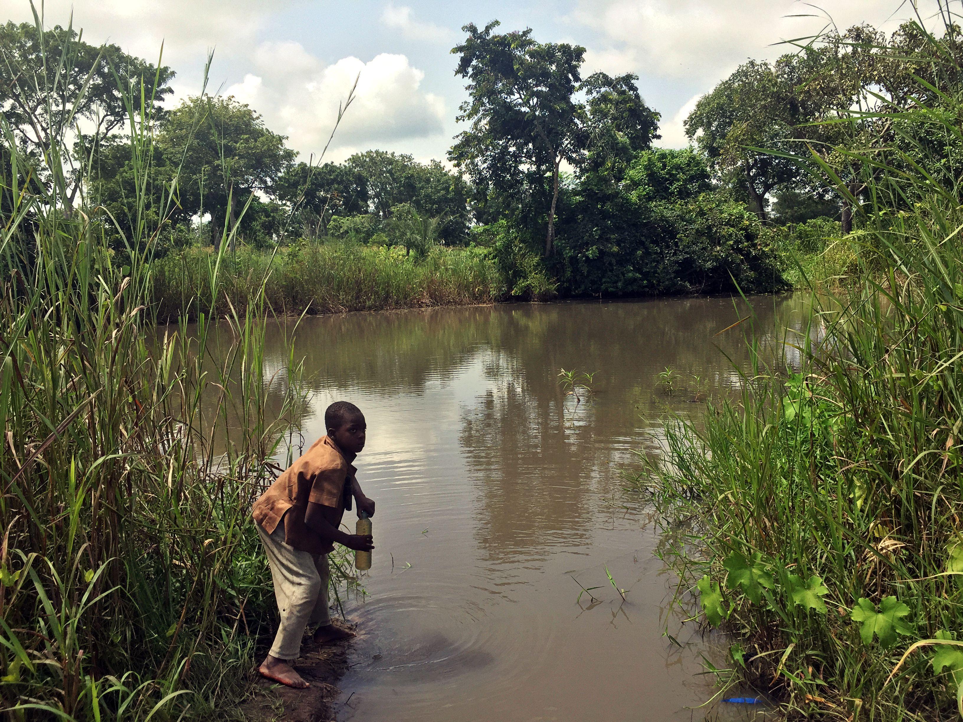 Kind trinkt verschmutztes Wasser aus einem See